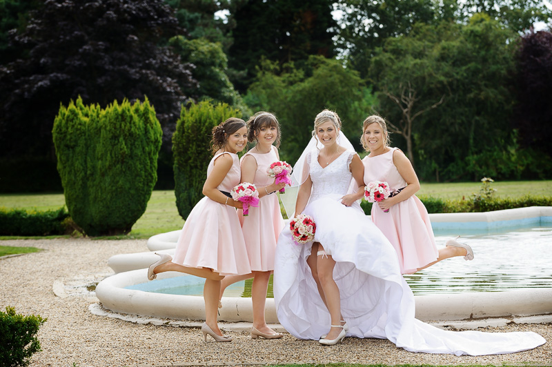bride and bridesmaids having fun at down hall in hertfordshire