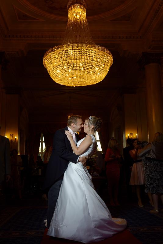 wedding portrait in down hall under chandelier